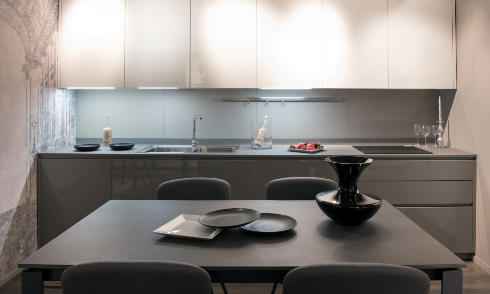 Compact modern grey and white fitted kitchen with illuminated cabinets and a dining table set with ceramics