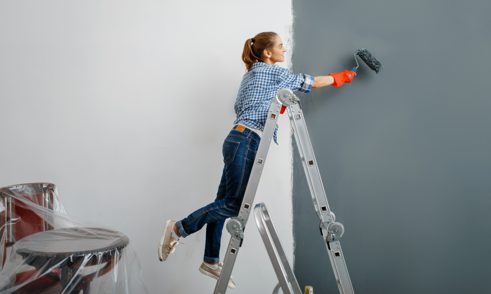Female house painter in gloves paints the wall. Home repair, laughing woman doing apartment renovation, home renovation
