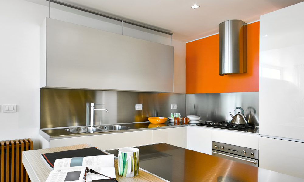 Interiors shot of a modern kitchen with orange feature cabinet, steel hood and kitchen island