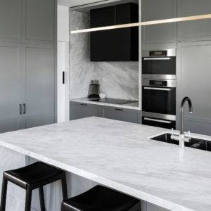Minimalist kitchen with quartz surface countertop and backsplash, grey panel kitchen cabinets