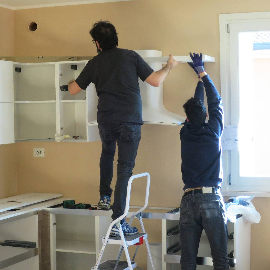 Two kitchen contractors installing kitchen cabinets