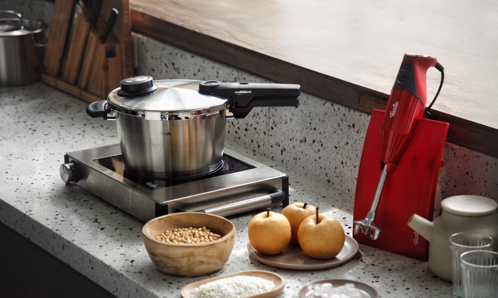 Portable kitchen stove with pot and cooking ingredients on a terrazzo kitchen countertop
