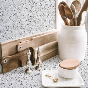 Dainty kitchen utensils in pretty white jar and containers against a terrazzo backdrop