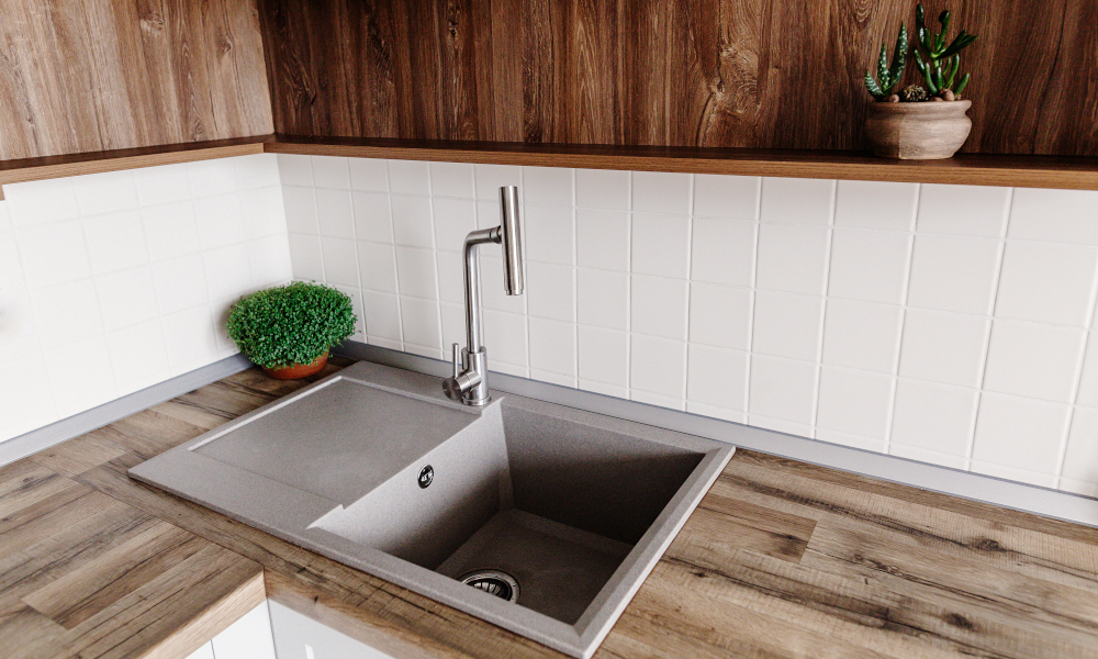 Stylish gray sink with metal faucet on modern kitchen with wooden tabletop and plants. Stylish kitchen furniture in grey color in Scandinavian style