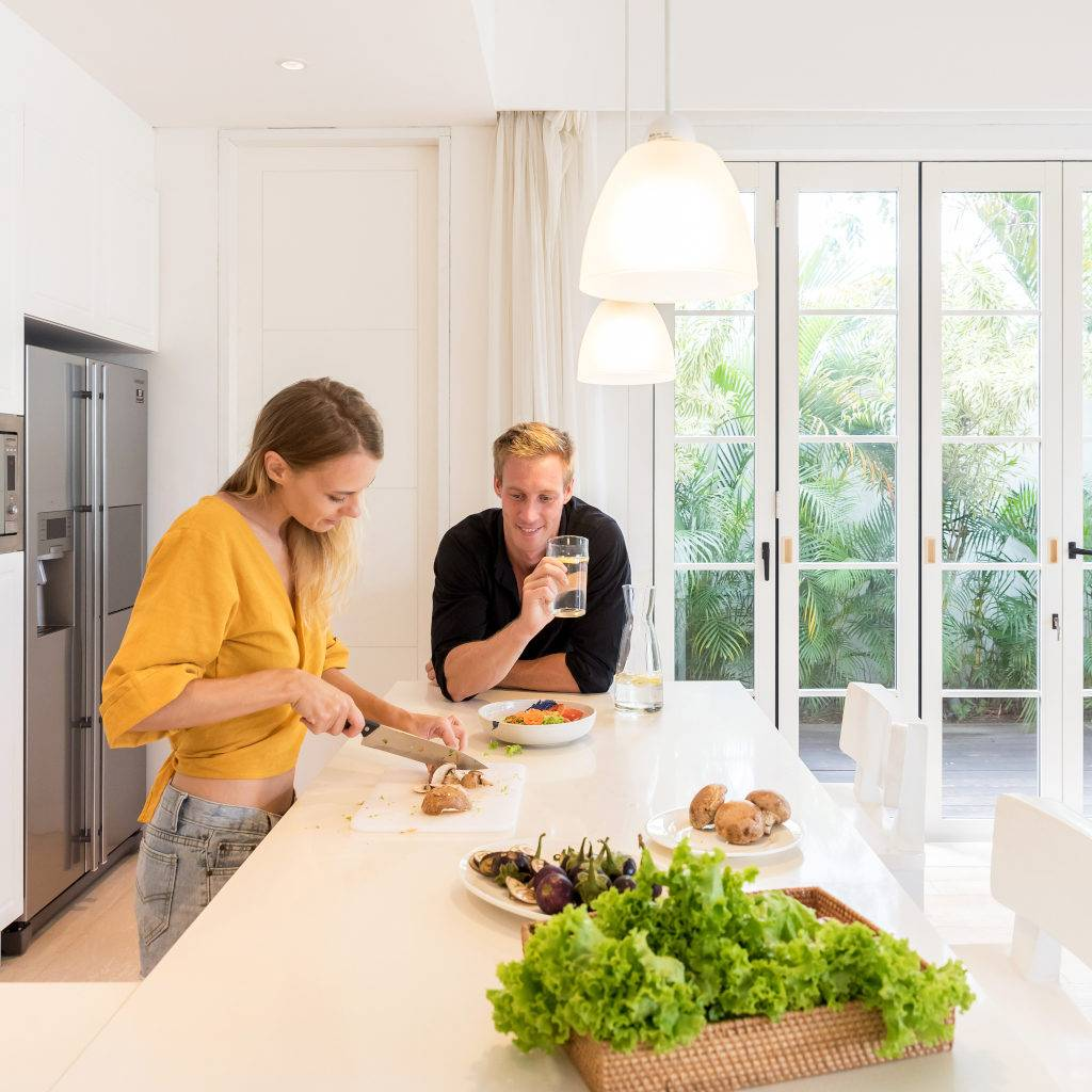 Couple making salad lunch on a white island kitchen at home