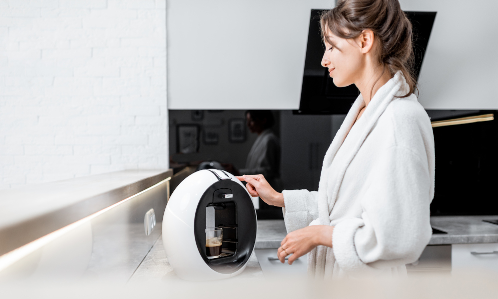 Young woman in bathrobe making coffee with a coffee machine on the kitchen countertop at home
