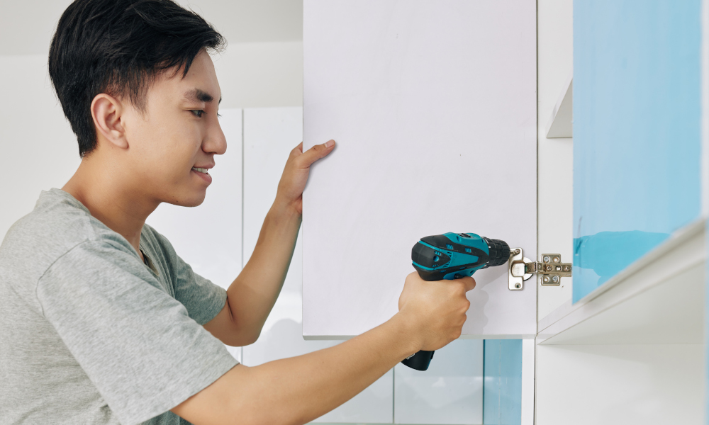 Young man using electric screwdriver when assembling cupboard in kitchen