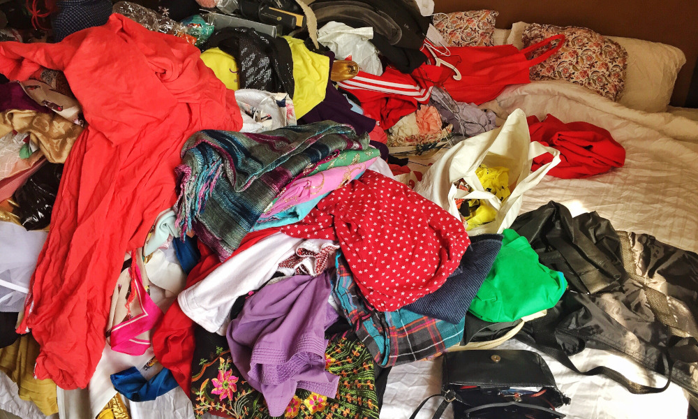 A bed full of messy clothes in preparation for decluttering