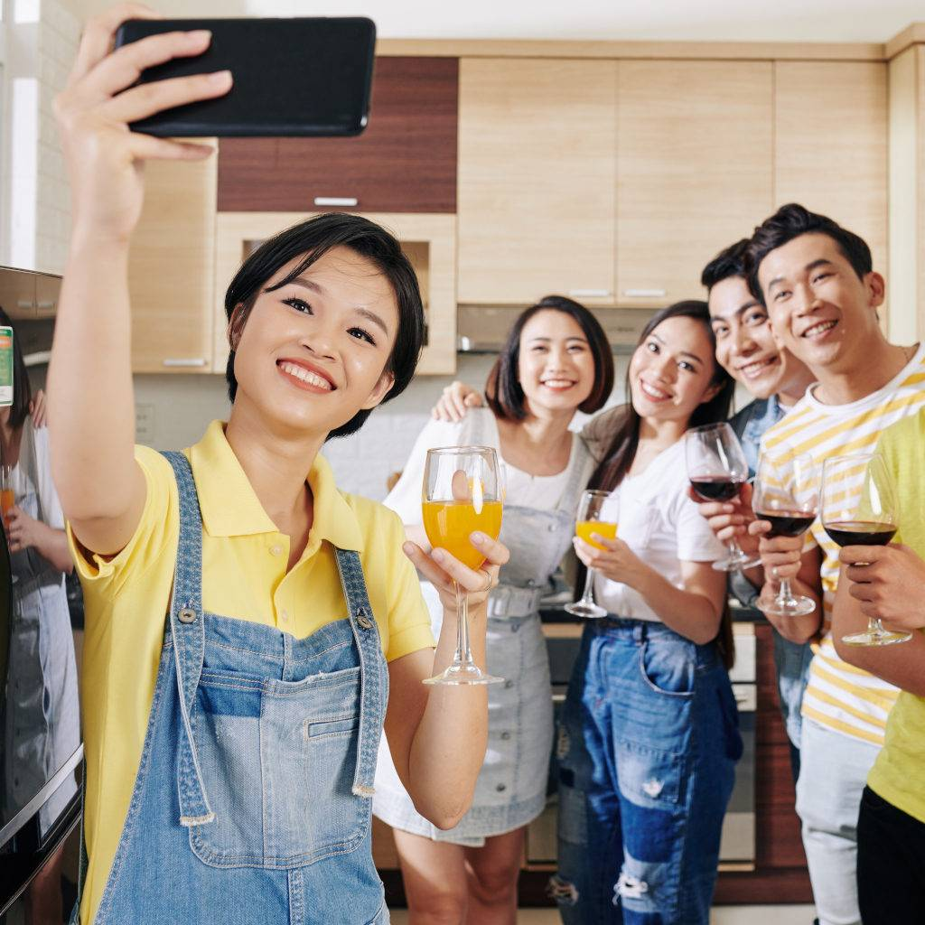 Friends with glass of orange juice taking selfie with her friends at house party