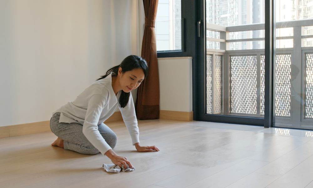 Woman cleaning the floor after dusting the ceiling and fan