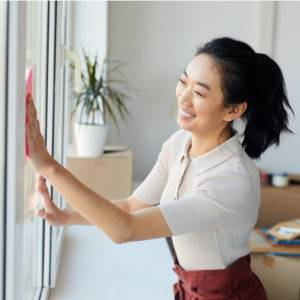 Young lady wiping the windows during spring cleaning