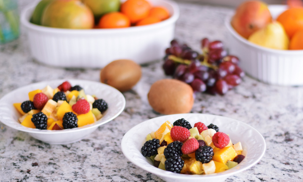 Bowls of cut fruits on a granite countertop