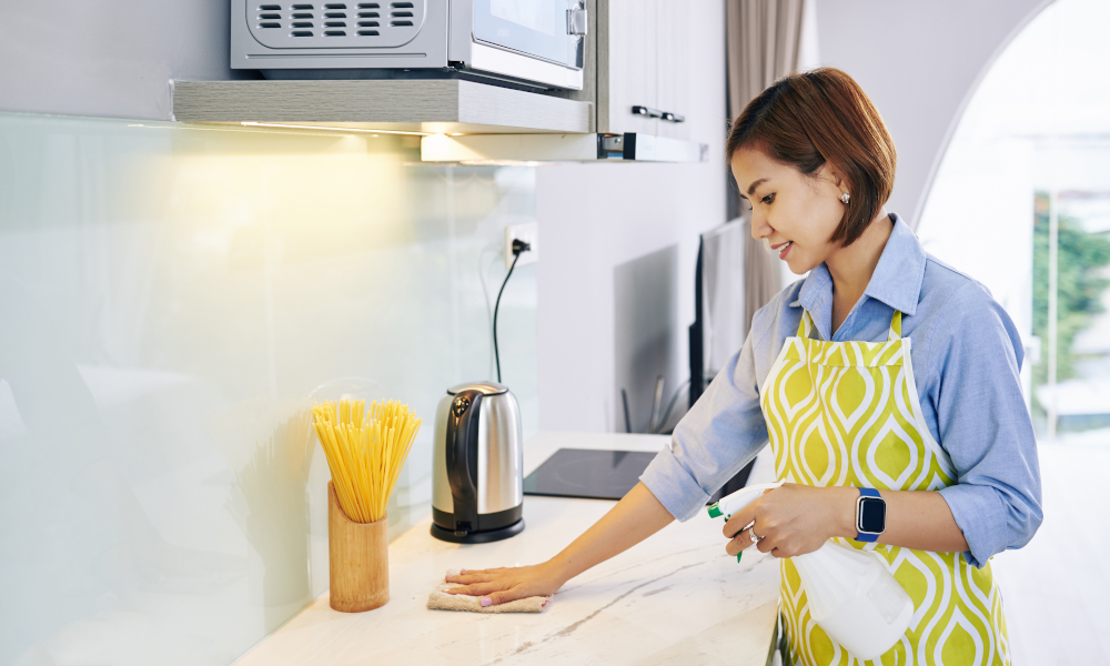 Smiling housewife spaying cleaning deterent on surface of kitchen counter and wiping it with soft cloth