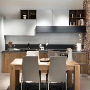Compact modern kitchen or kitchenette with built in cabinets and appliances open plan to a small contemporary design chunky table and chairs