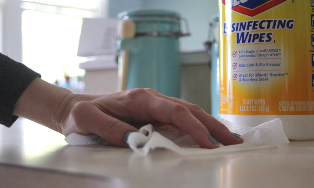 Wiping the countertop with disinfecting wipes