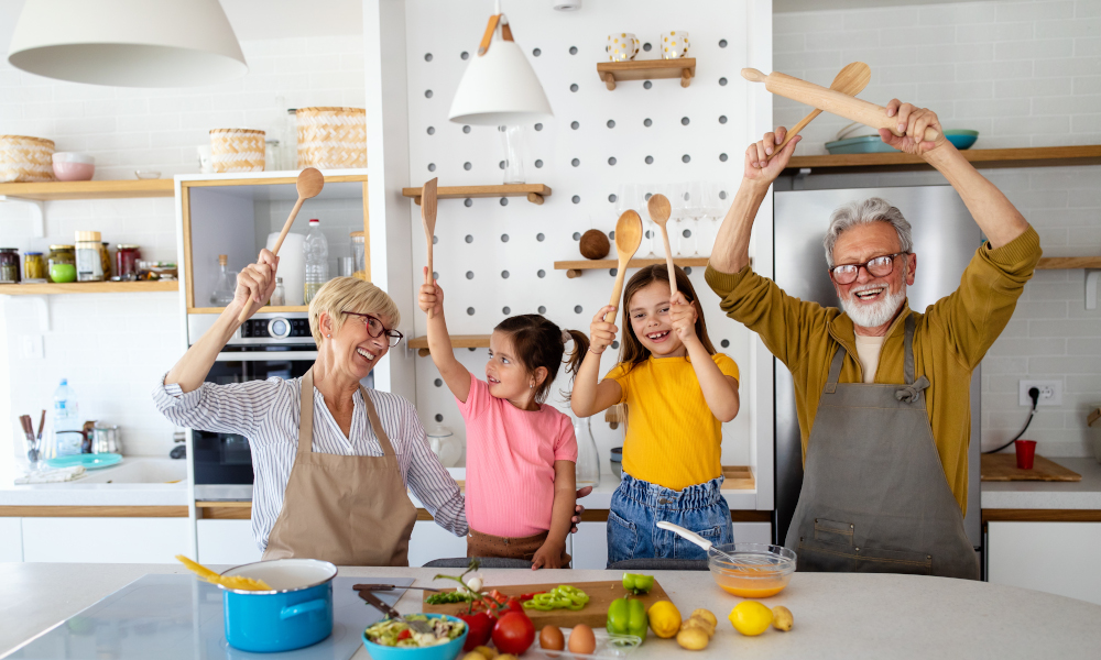 Cheerful grandparents and grandchildren spending good time together while cooking in kitchen