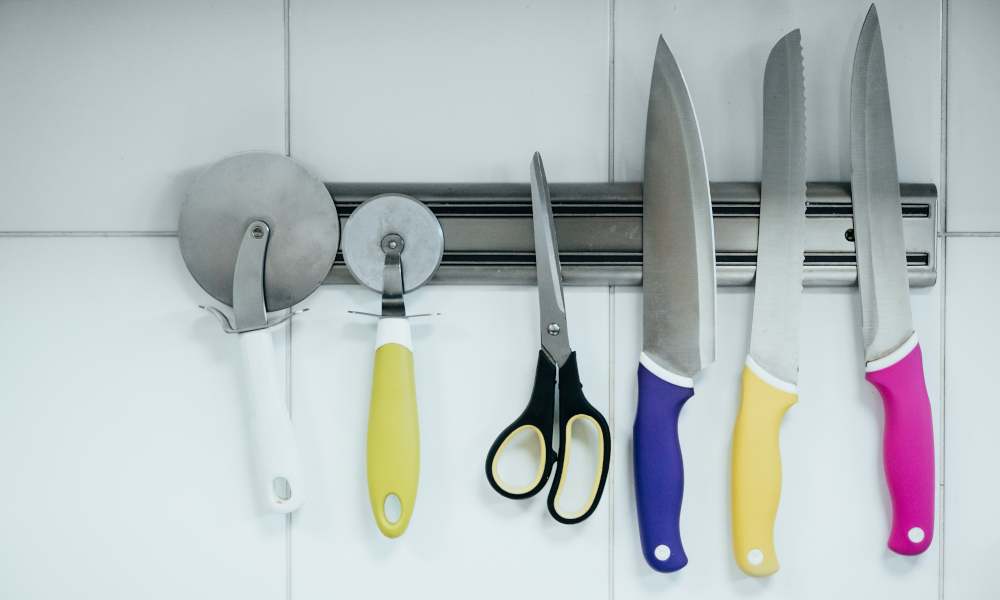 A variety of kitchen knives baker's appliances on a magnetic holder on the wall