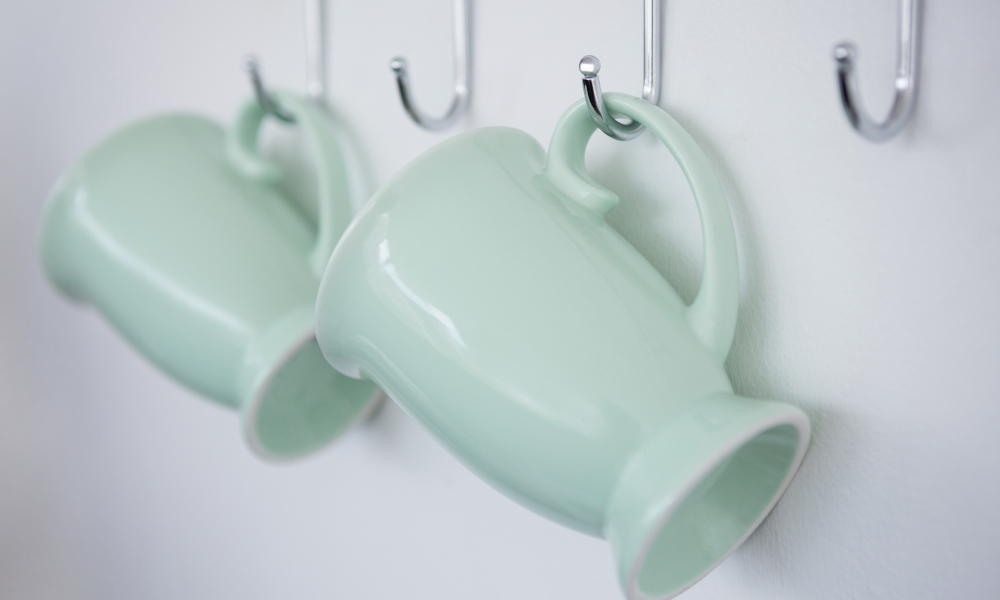 Mugs hanging on kitchen hook rail against white wall