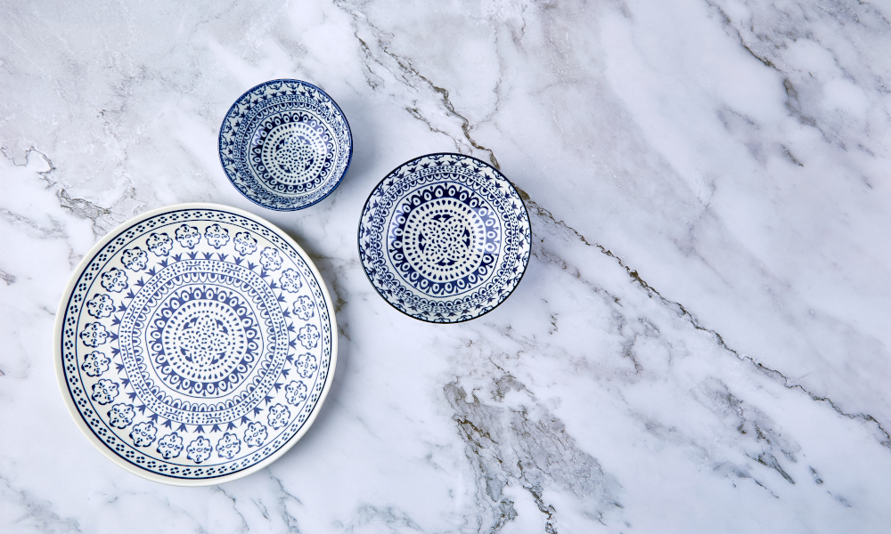 Set of modern trendy blue plates on marble countertop