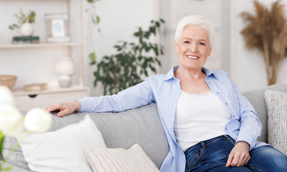 Smiling Elderly Lady Posing On Couch In Living Room At Home, Looking At Camera