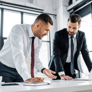 Businessmen having discussion while standing near desk in modern office