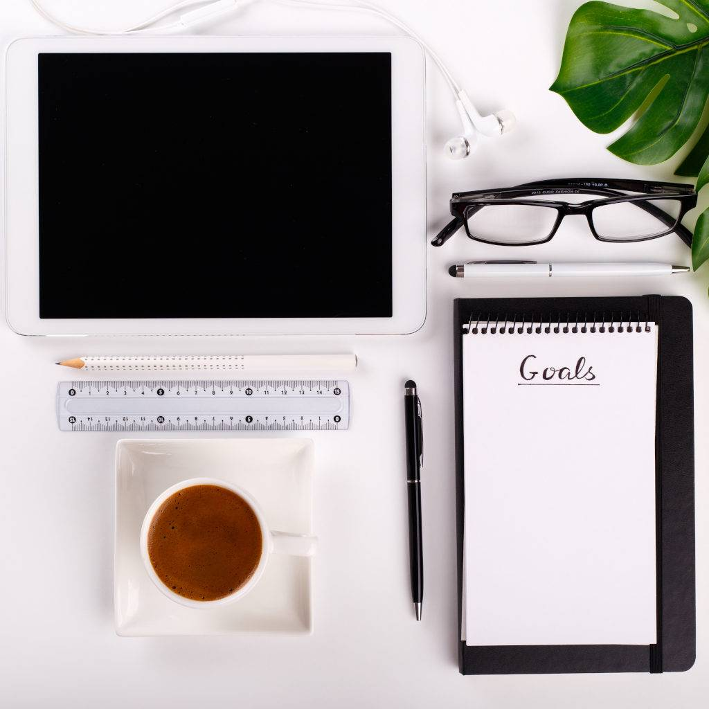 Modern white office desk table with tablet, eyeglasses, pen, pencil, ruler, monstera plant, notepad and greek cup of coffee