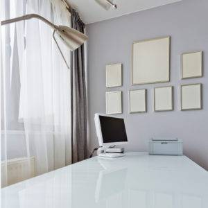 White long desk top with computer in grey minimalist interior with empty picture frames