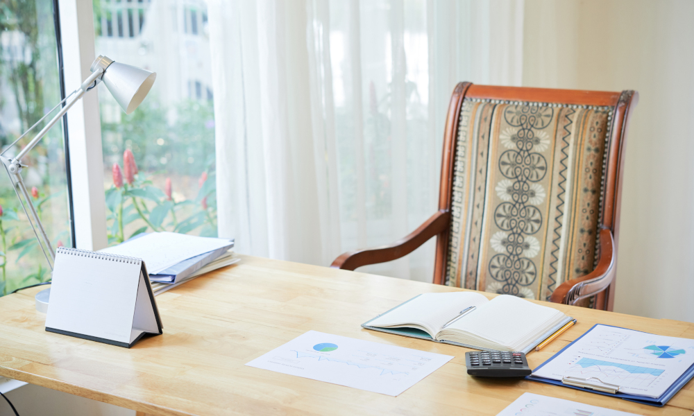 Interior shot of comfortable chair at wooden table with composed papers and notepad on desk near window