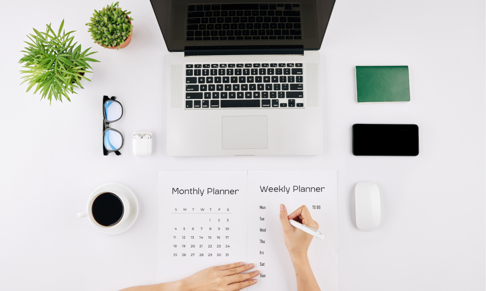 Hands of young female entrepreneur checking calendar and filling weekly planner