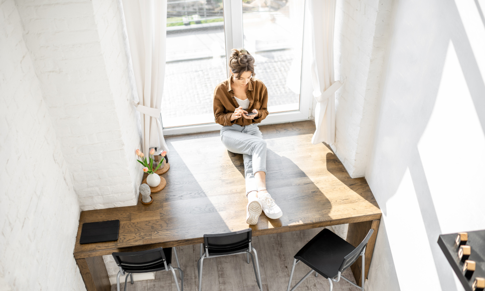 Woman sitting with phone on the huge window sill at home, view from above