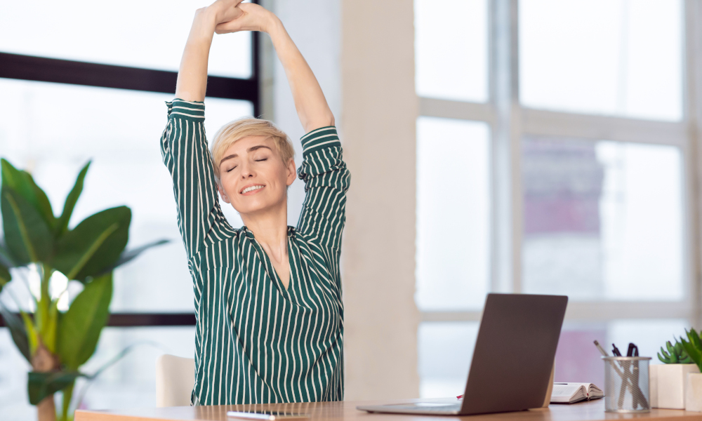Break At Work. Entrepreneur Lady Stretching Hands With Eyes Closed Working At Laptop Sitting In Modern Office.