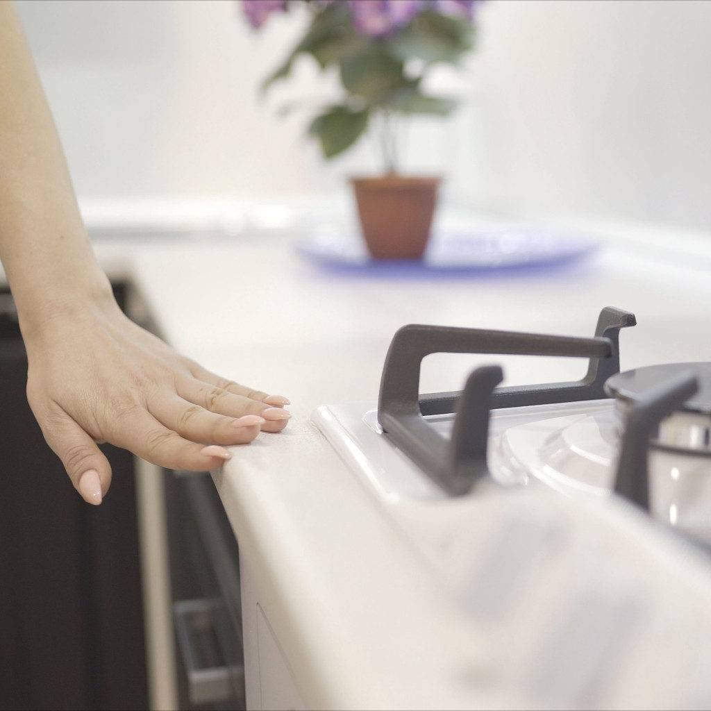 Woman touching the rounded edge and smooth finishes of a clean pristine kitchen countertop