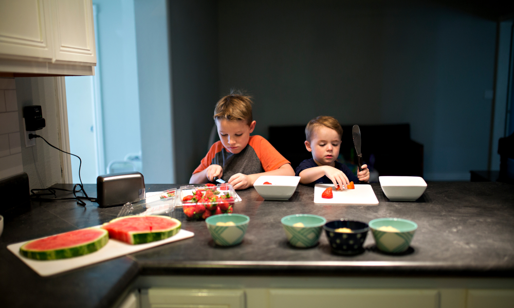 Two young boys cutting strawberries at the kitchen countertop