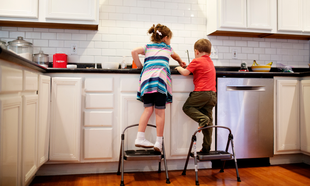 Two siblings brother and sister standing on the stool to wash the dishes