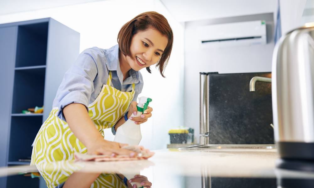 Cheerful young lady cleaning kitchen counter with disinfectant