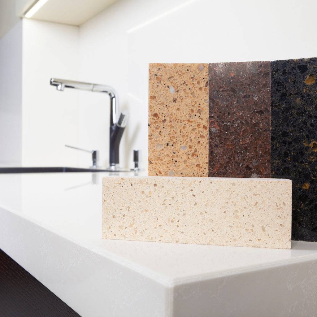 Different quartz kitchen counter top samples on white polished countertop with precise processed edges