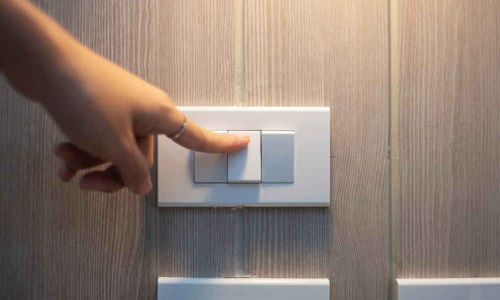 Female finger is turn on or off on light switch on white wall at home. Energy Saving, power, electrical and lifestyle concepts