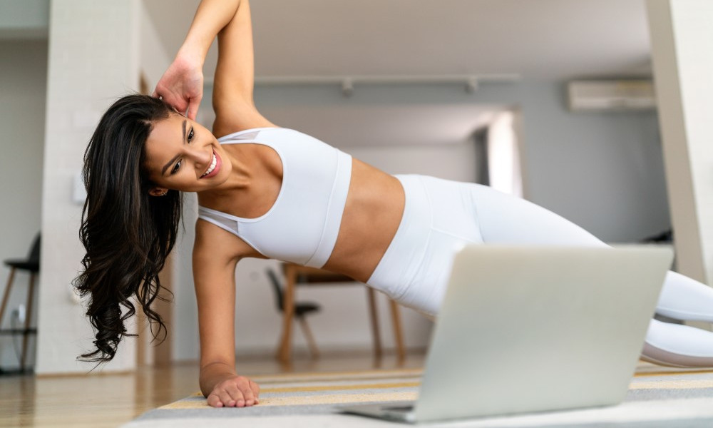 Beautiful fit happy woman exercise fitness at home instead of going to the gym.