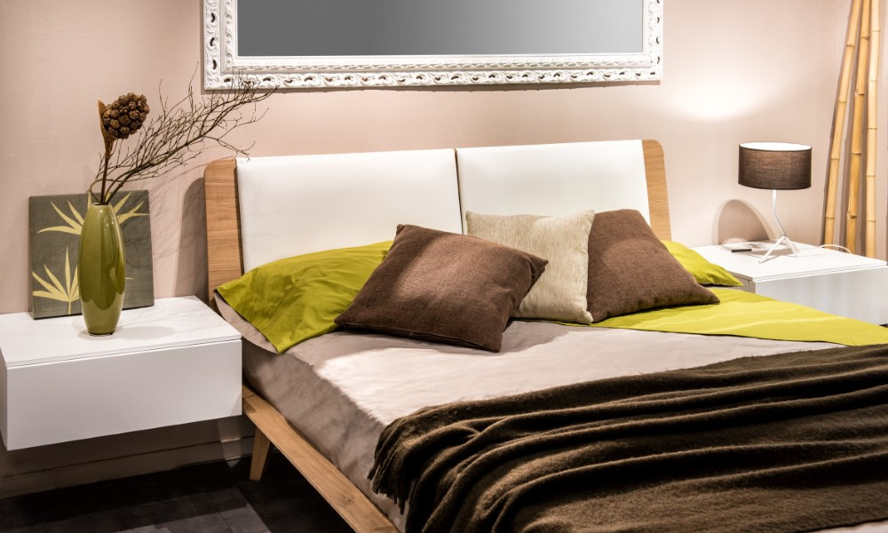 Bedroom interior with four pillows on bed and mirror on wall