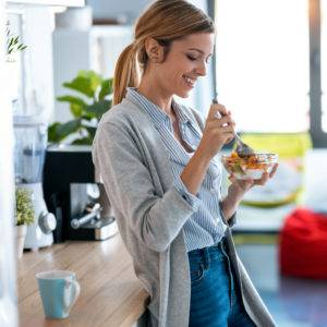 Pretty young woman having healthy breakfast in the kitchen at home