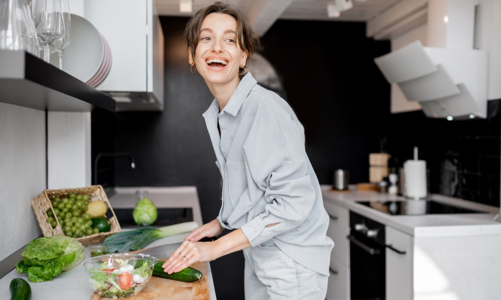 Young and cheerful woman cooking food with healthy vegetarian ingredients on the kitchen at home