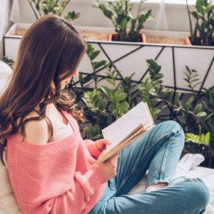 Young woman reading book while sitting surrounded by green plants at home