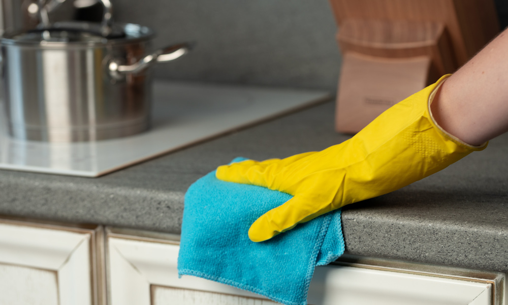 Hand in yellow glove cleaning old kitchen countertop
