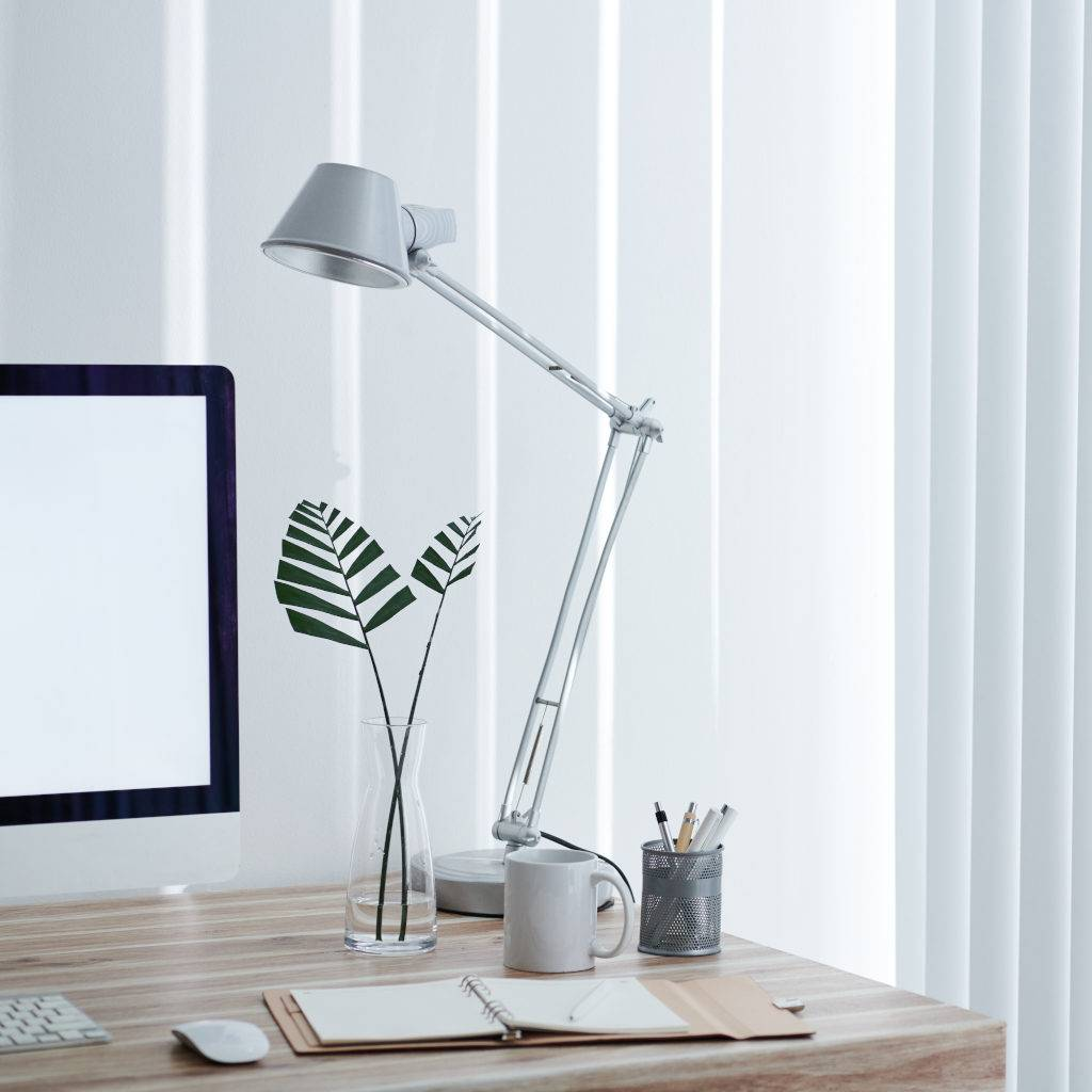 Home office desk of entrepreneur with lamp, computer monitor, planner and cup of coffee