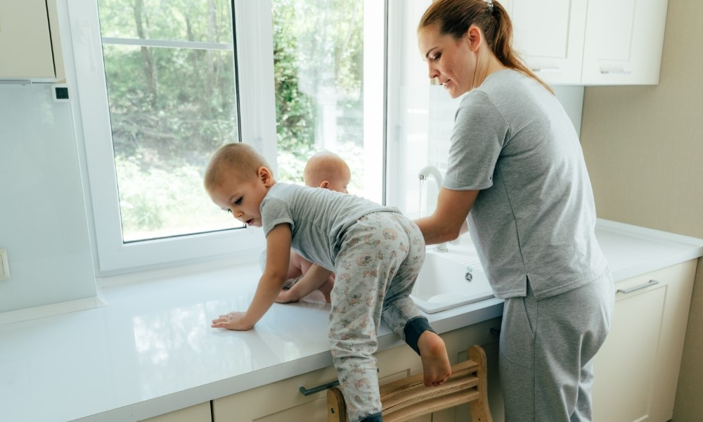 Mother trying to work in the kitchen with young children climbing onto the countertop