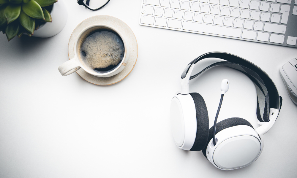 Home office desk workspace with Headphones, glasses, coffee and keyboard on white background