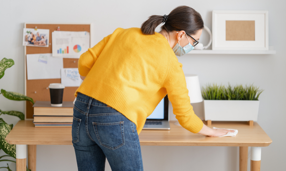 Woman in facemask cleaning her desk before working in home office