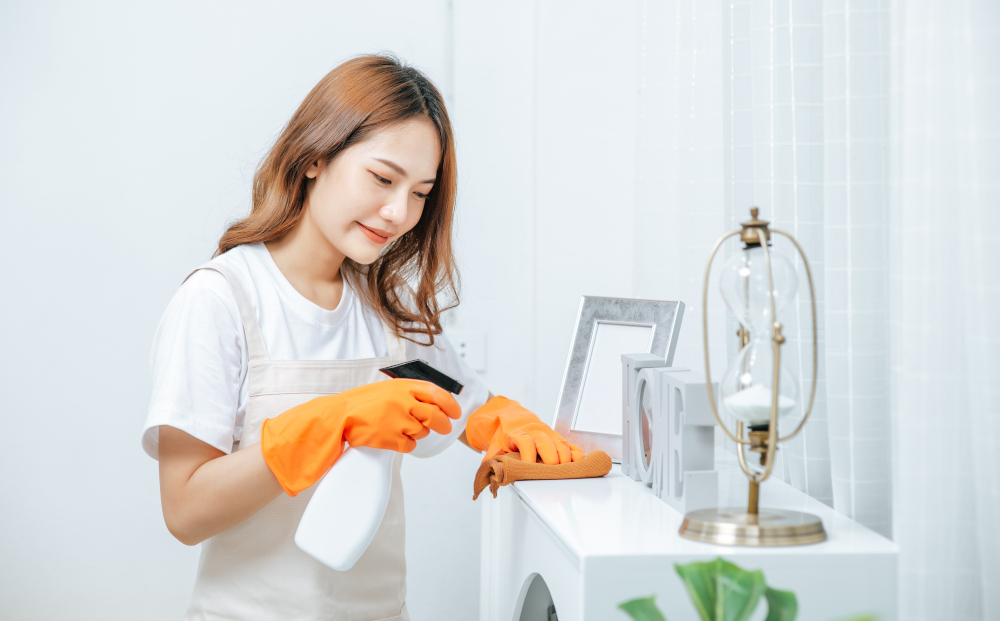 Young housekeeper woman wearing apron and rubber gloves use cleaning solution in a spray bottle on white furniture