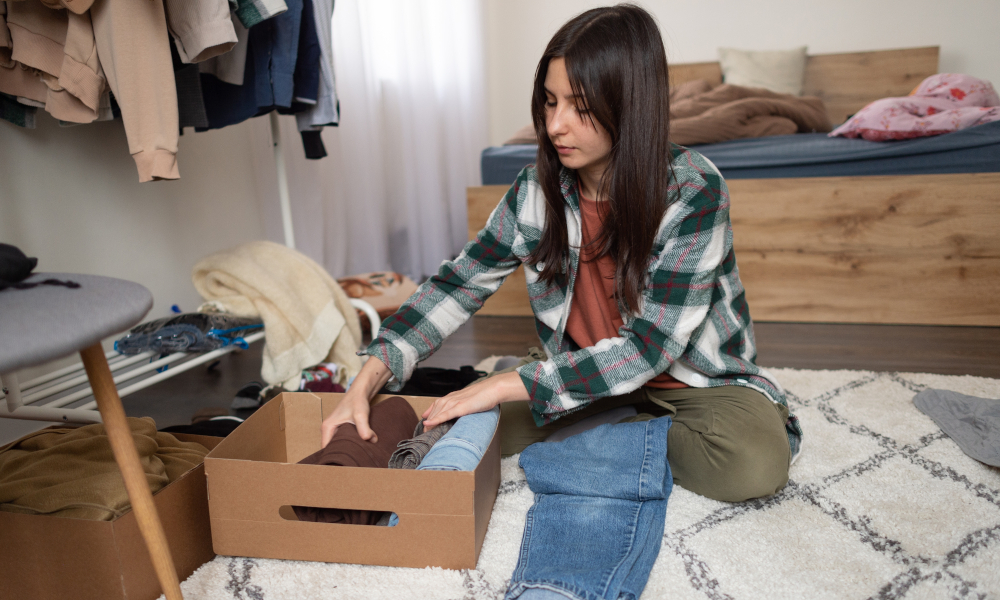Woman tidying and organising clothes in the bedroom using Konmari method