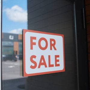 Placard For Sale hanging on the door of modern home